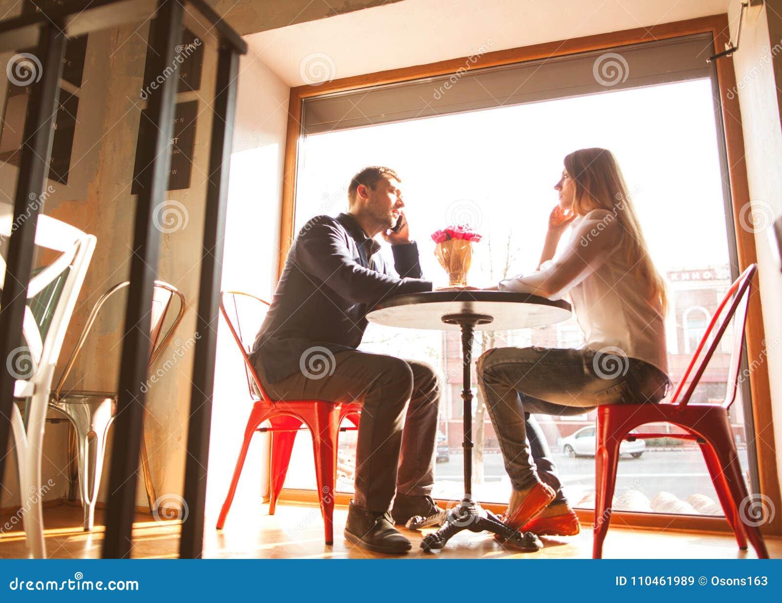 Grabben med en flicka i ett kafé på dag för St-valentin` s, en grabb ger a