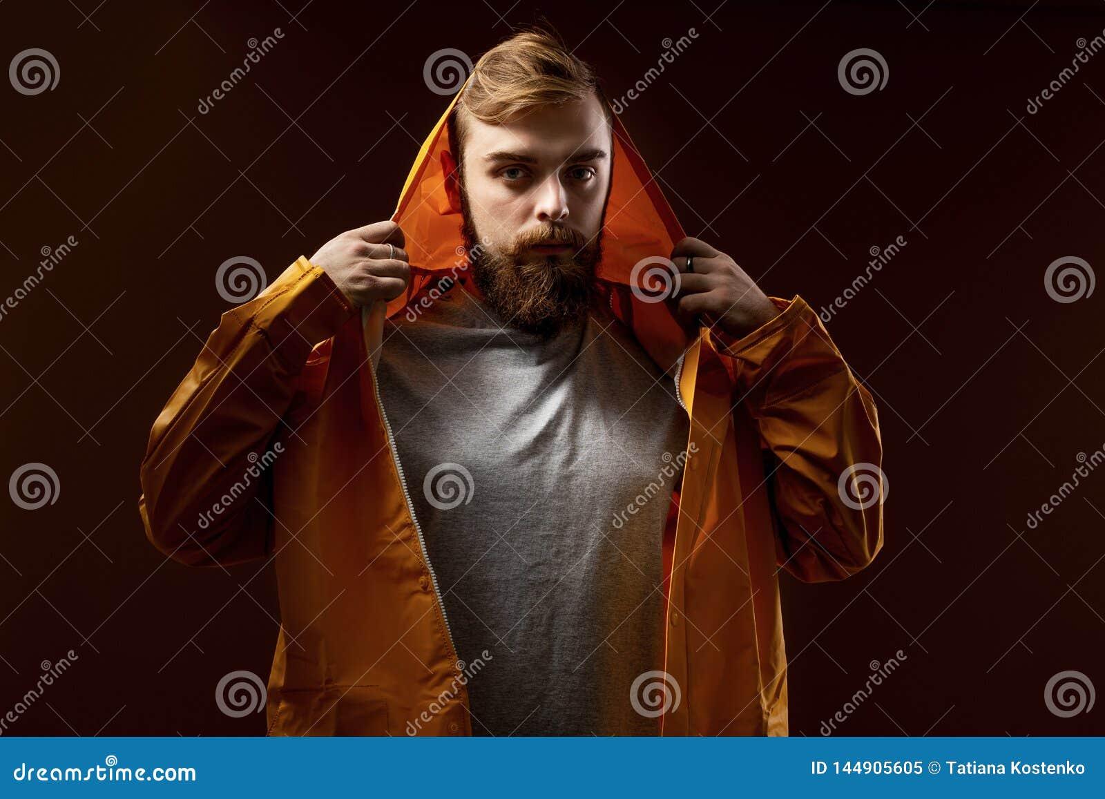 Grabben med ett ikl?dda sk?gg och mustasch en gr? t-skjorta och ett gult omslag med en huv st?r p? en brun bakgrund