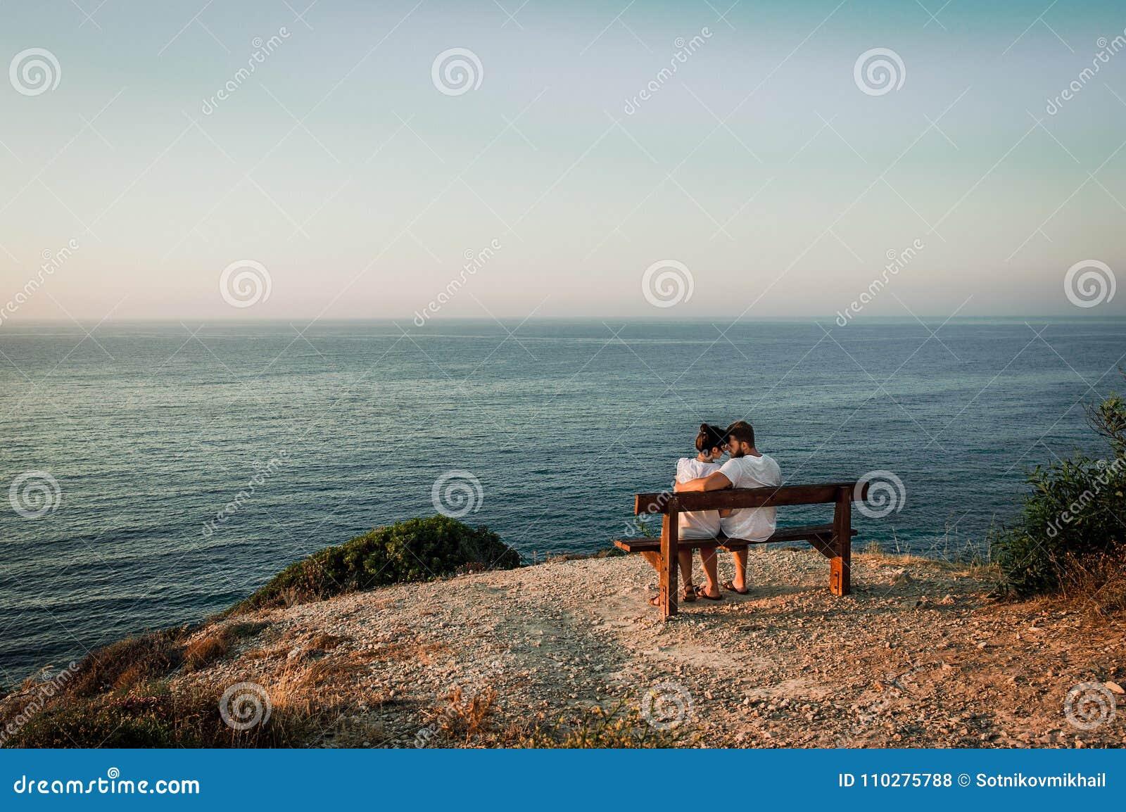 Grabben och flickan möter de första strålarna av solen på havet