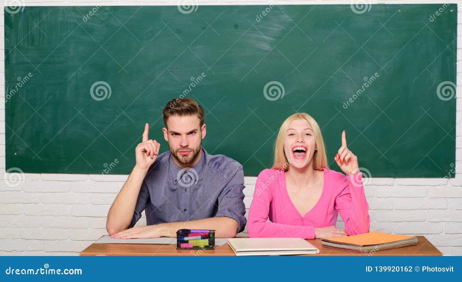 Grabben och flickan sitter på skrivbordet i klassrum Korrekt svar på deras mening Studera i högskola eller universitet Applicera