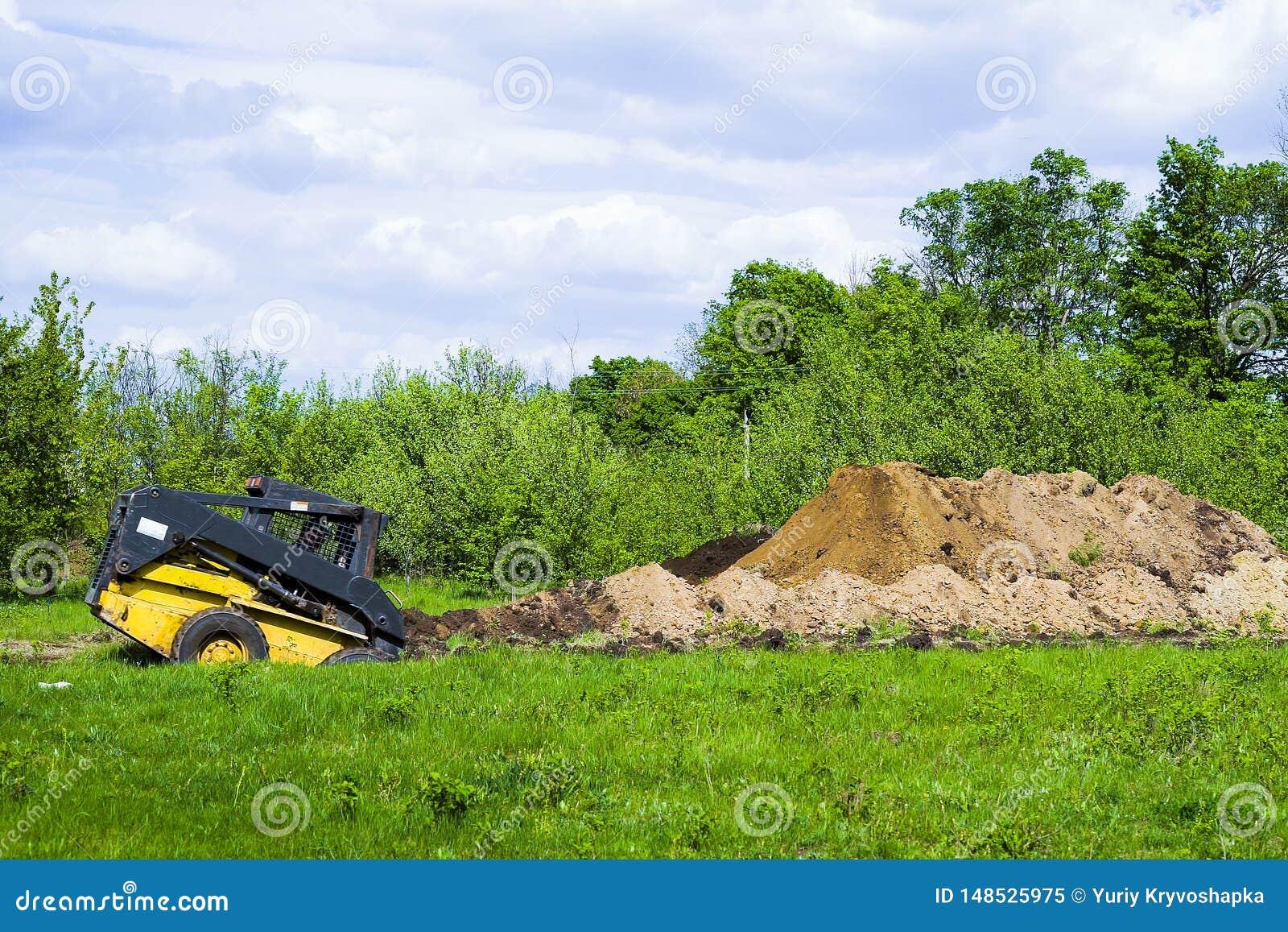 Grabende Grube des Baggers auf grasartigem Feld mit Garten auf Hintergrund