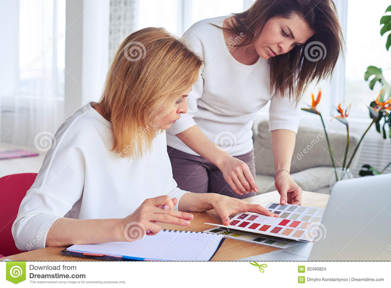 Graceful concentrated females looking through catalog of color p