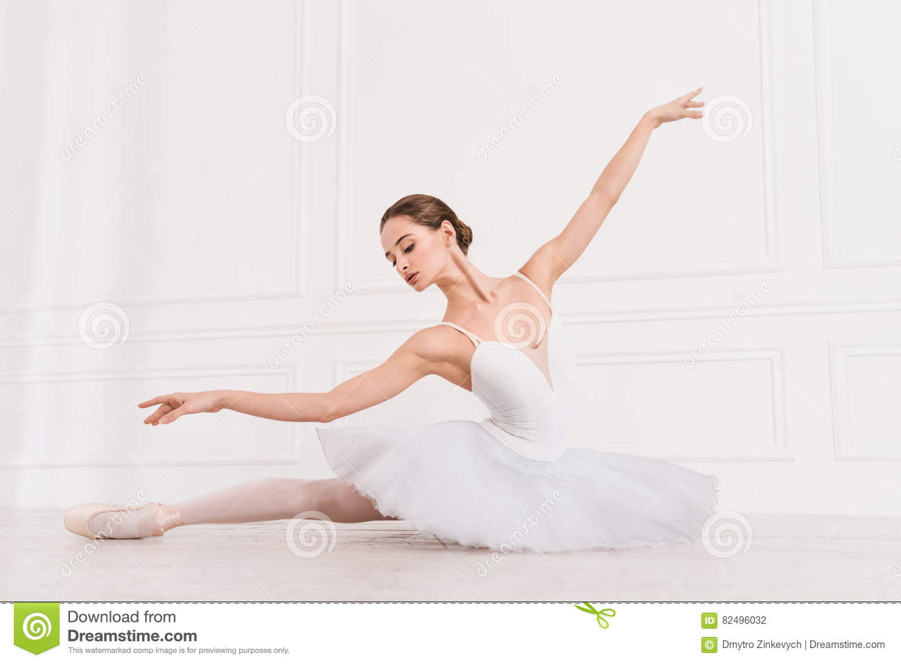 336d496acbb619 Serious young ballerina wearing white leotard with fluffy skirt looking  down while stretching her leg on the floor