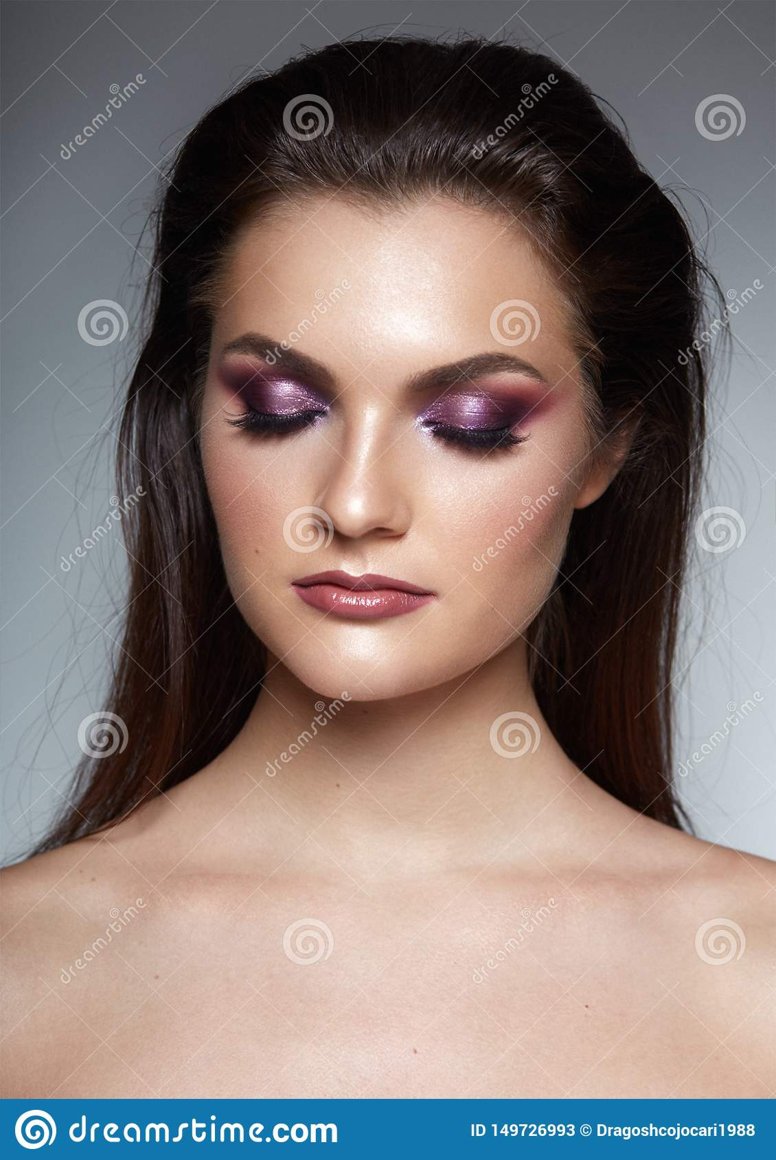 Graceful young woman with cosed eyes, poses confident with hairstule and perfect make up, isolated on a gray background.