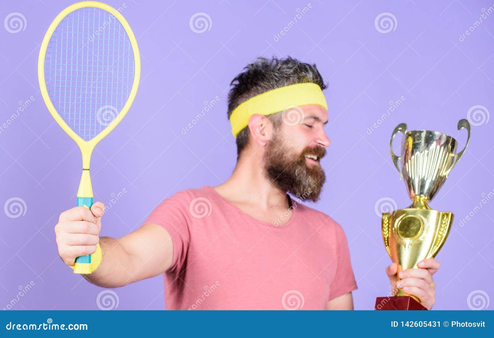 Gracz w tenisa wygrany mistrzostwo Atleta chwyta tenisowy kant i z?ota czara Wygrana tenisa gra M??czyzna modnisia brodata odzie?