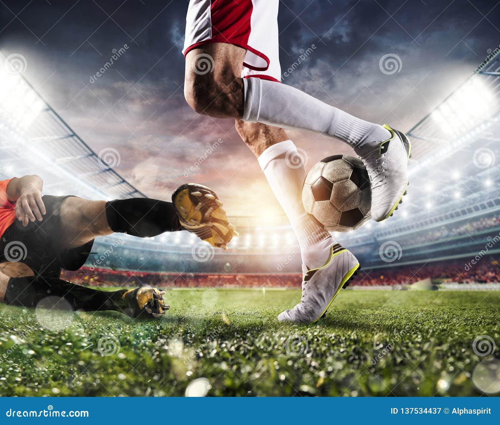 Gracze piłki nożnej z soccerball przy stadium podczas dopasowania