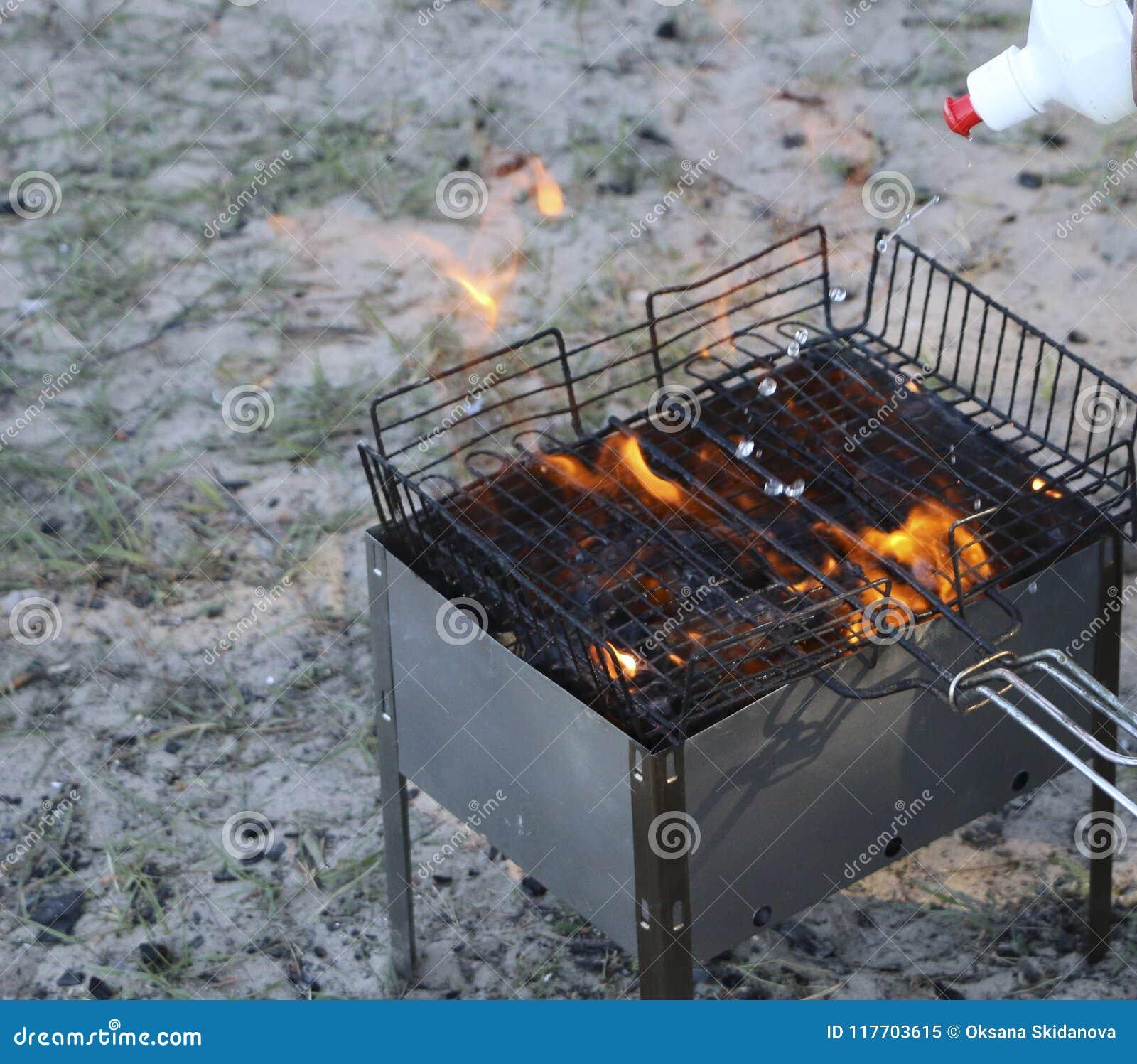 Grade ardente no soldador com carvões quentes é uma grade os carvões são molhados com um líquido especial para a combustão forte