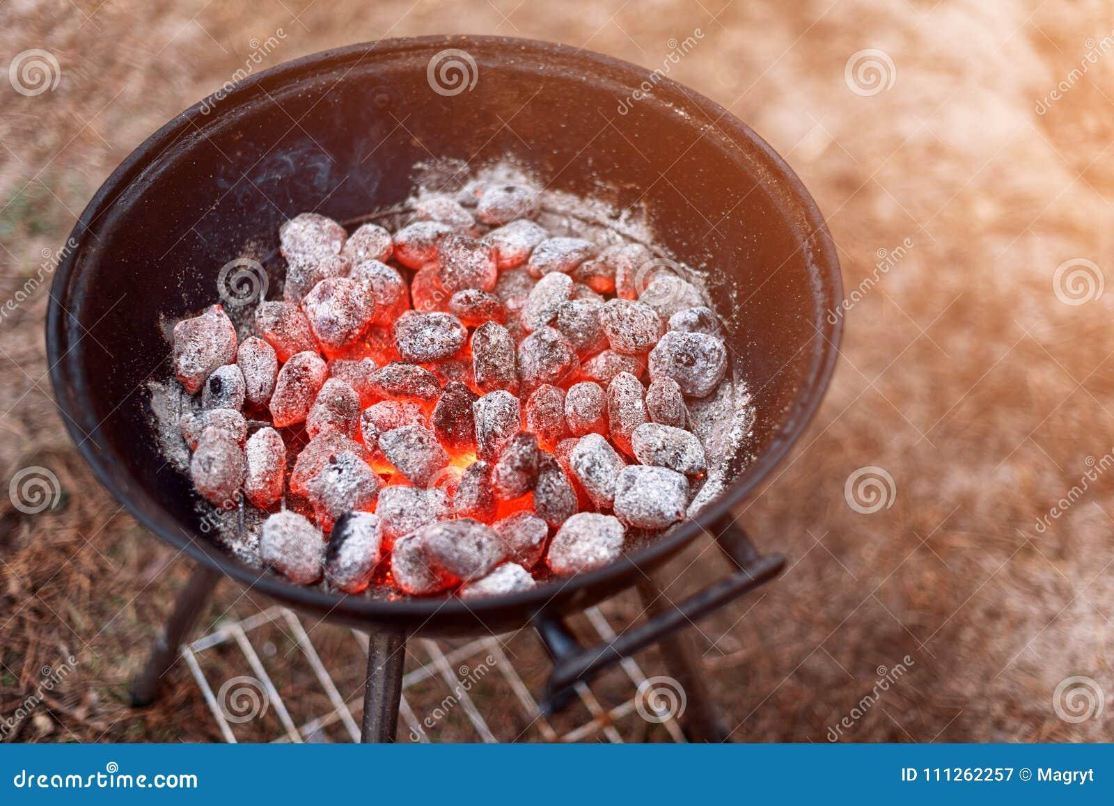 Grade do BBQ com incandescência e ardor de carvões amassados quentes do carvão vegetal, close up, vista superior
