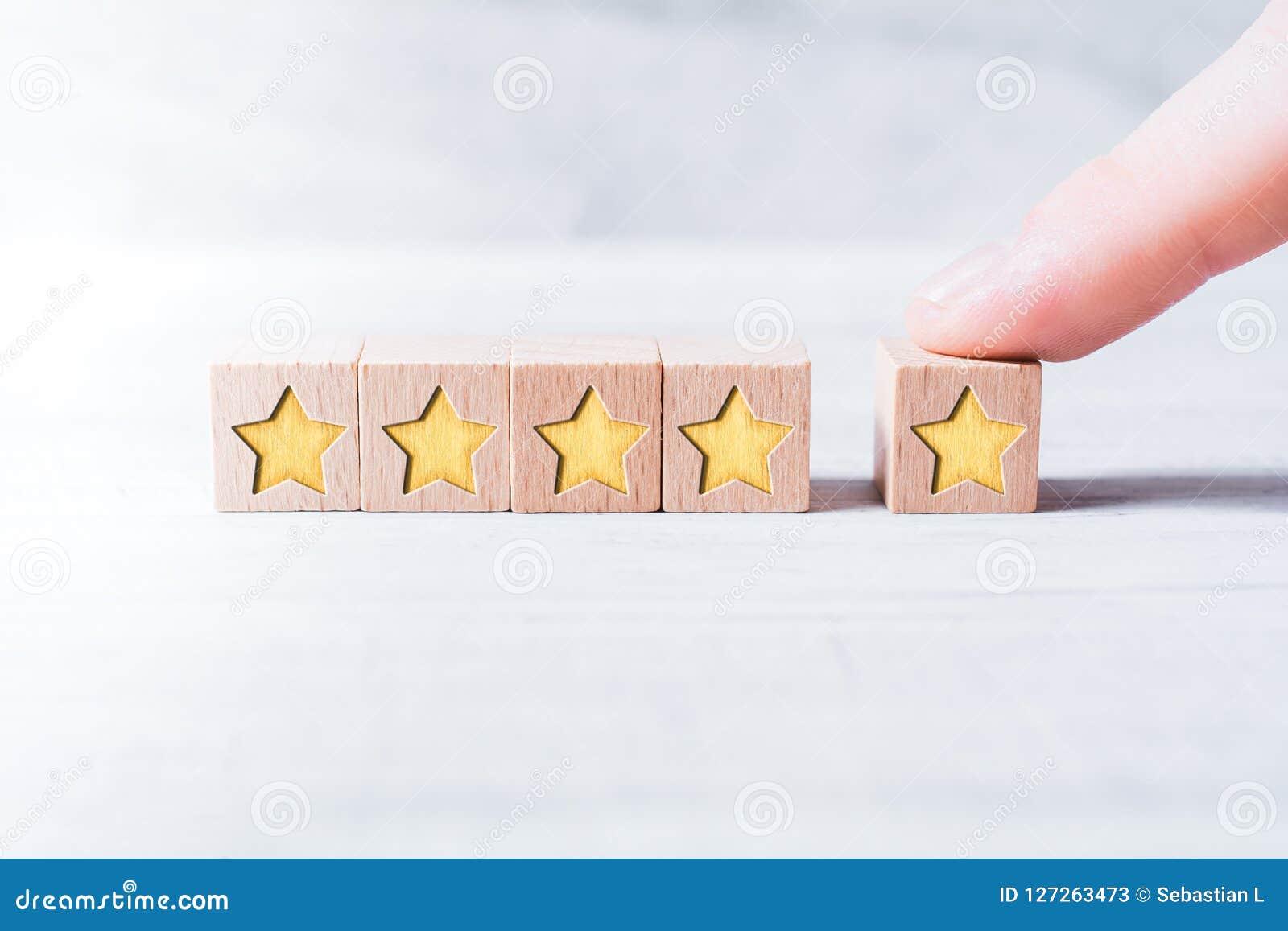 Graduación de cinco estrellas formada por los bloques de madera y dispuesta por un finger masculino en una tabla blanca