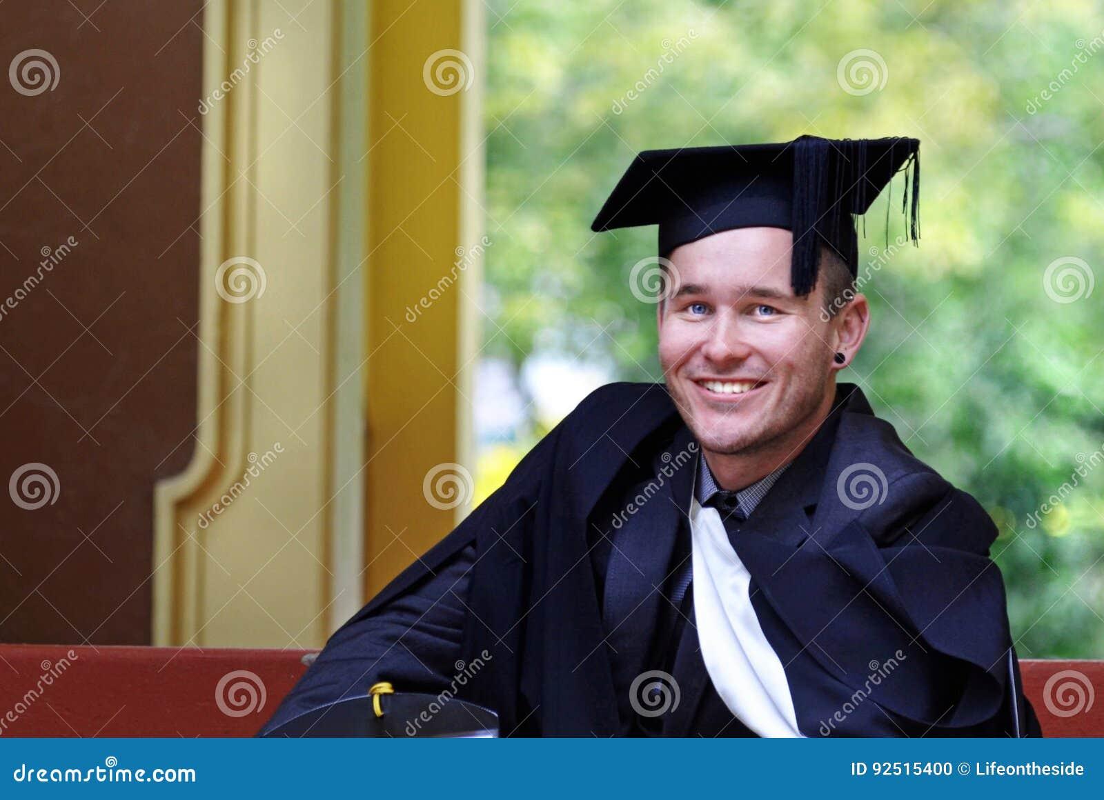 Graduado orgulloso de la universidad del hombre joven después de la ceremonia de graduación