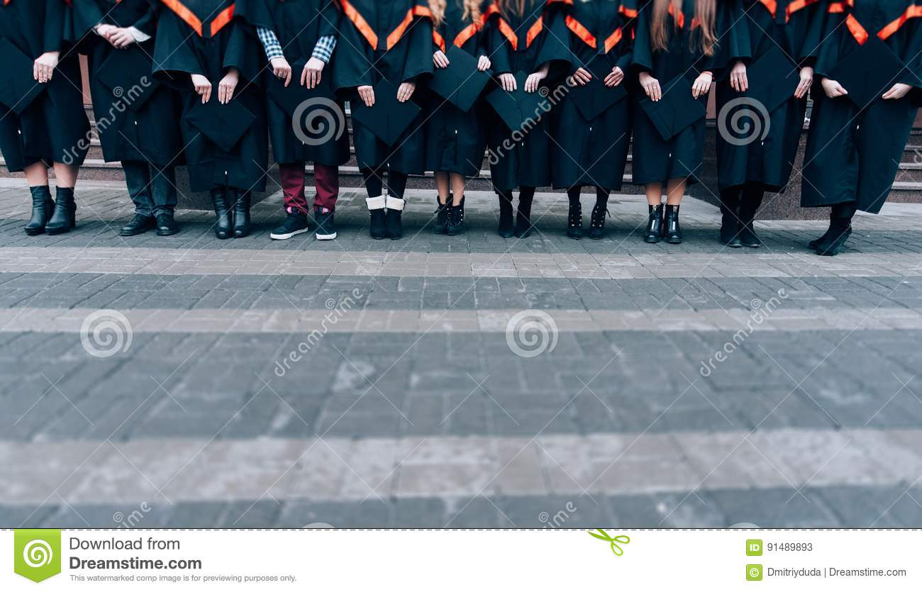 Graduates holding their hats in hands. Graduates wearing robes and hats in their hands. Group of students in bachelor gowns.