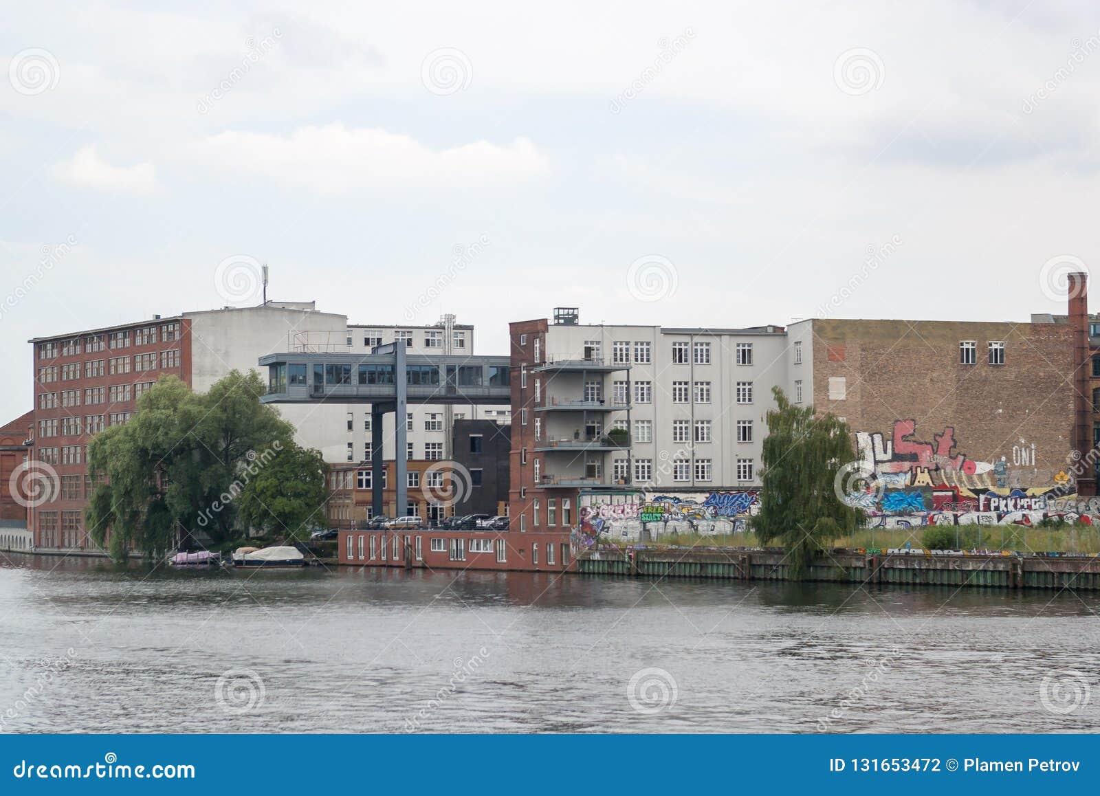 Graffiti-geschilderde baksteengebouwen dichtbij Fuifrivier in Kreuzberg, Berlijn
