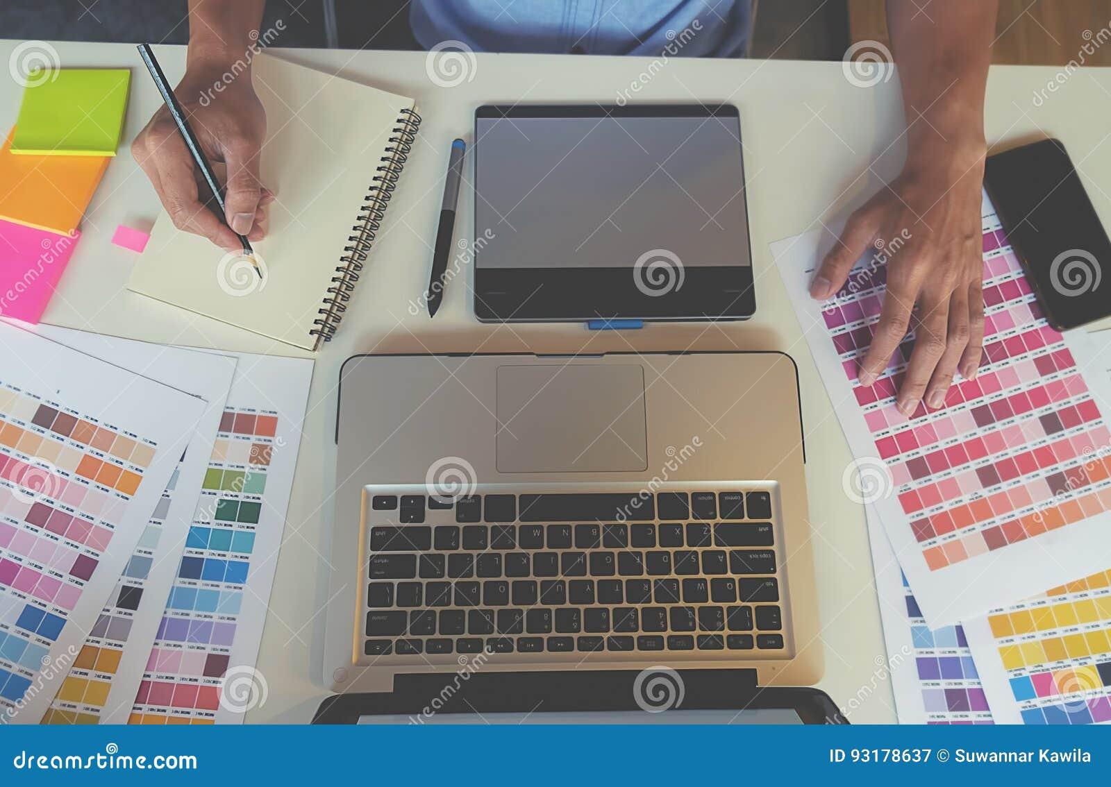 Grafisch ontwerp en kleurenmonsters en pennen op een bureau