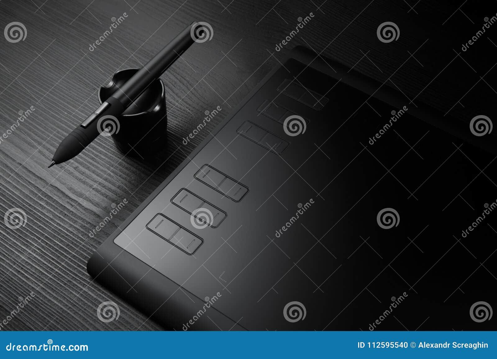 Grafische Tablette mit Stift für Illustratoren und Designer auf schwarzem hölzernem Hintergrund