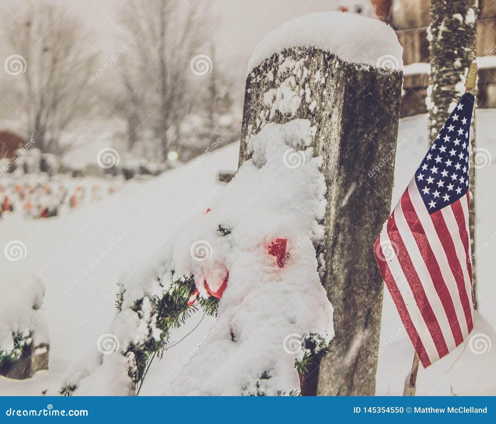 Grafsteen in de sneeuw met vlag
