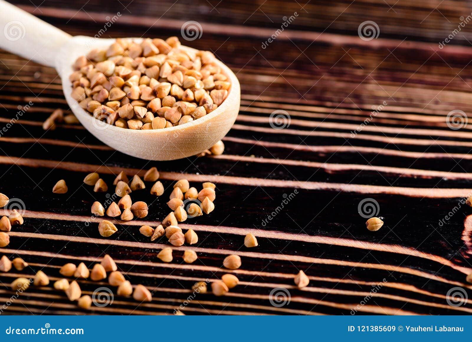 Graines crues de sarrasin dans la cuillère en bois sur la table en bois Eatin sain