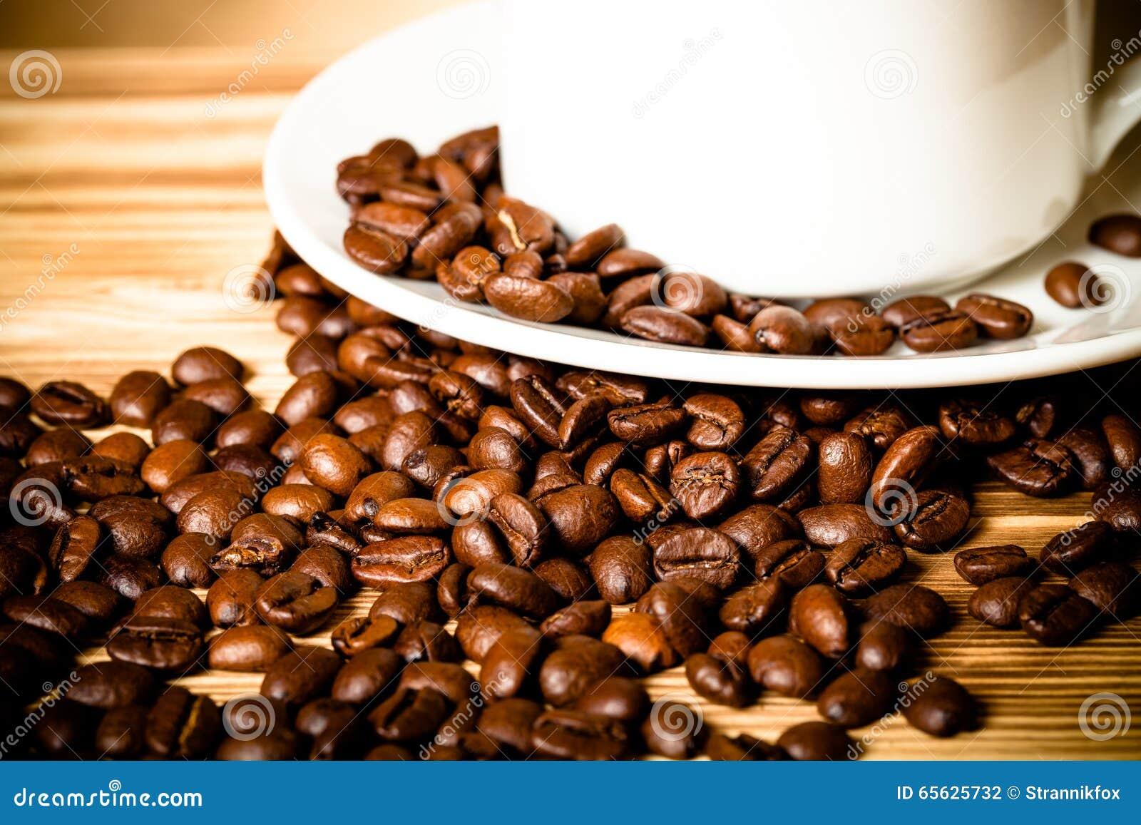 Grains de café et café dans la tasse blanche sur la table en bois pour le backgro