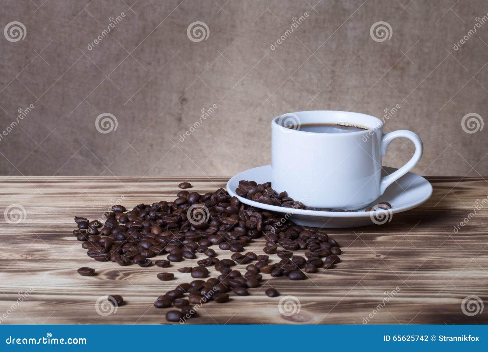 Grains de café et café dans la tasse blanche sur la table en bois vis-à-vis d a