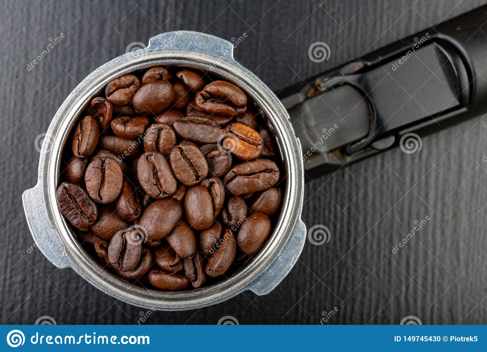 Grains de café rôtis noirs et un flacon de machine de café Accessoires pour le café de brassage sur une table de cuisine noire