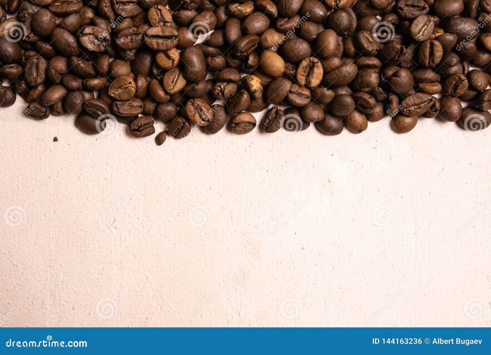 Grains de caf? r?tis en vrac sur un fond rose-clair le cofee fonc? a r?ti le caf? d arome de saveur de grain, fond naturel de mag