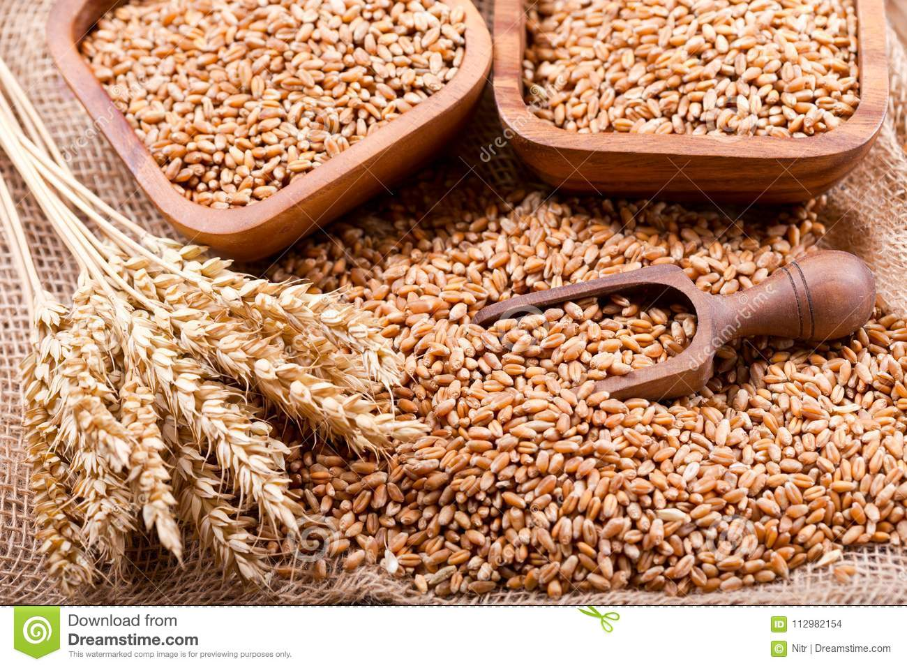 Grains and wheat ears on a wooden table