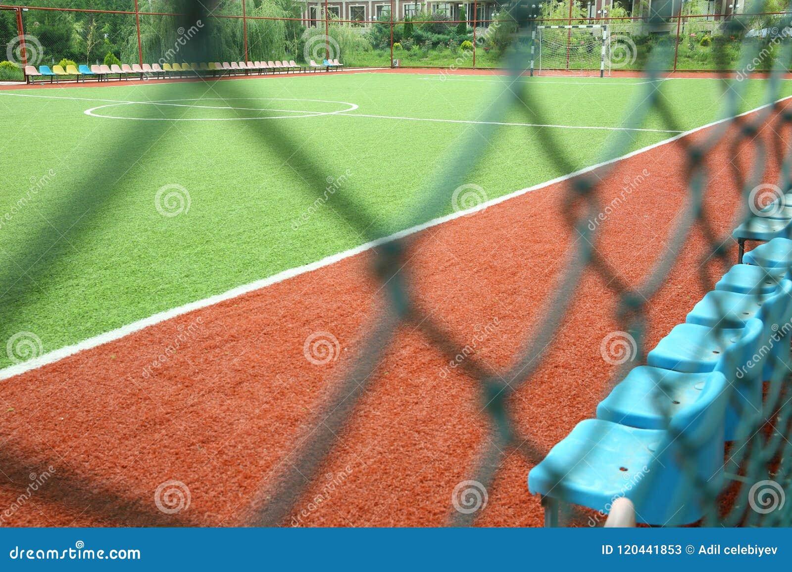 Grama artificial de Mini Football Goal On An Objetivo do futebol em um gramado verde Campo de futebol perto da cerca no dia ensol