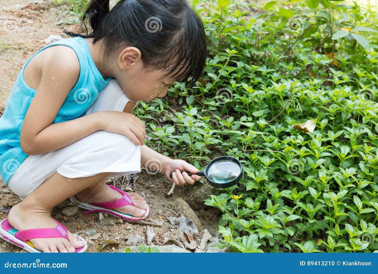Grama de exploração da menina chinesa asiática com lupa