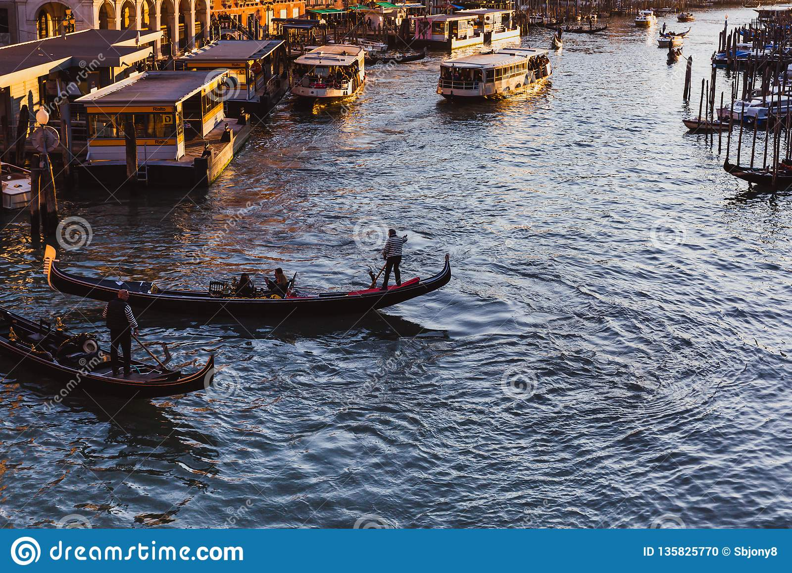 Gran Canal famoso del puente de Rialto en puesta del sol en Venecia, Italia