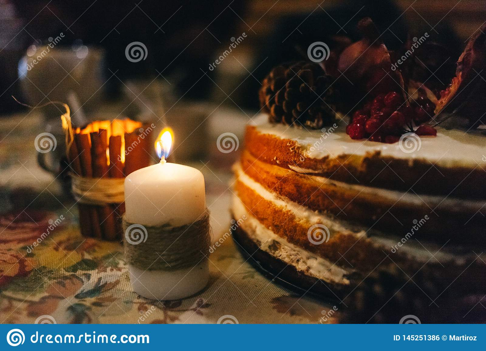 Granaatappel gelaagde cake in het licht van een dikke die kaars in een hennepkoord wordt verpakt