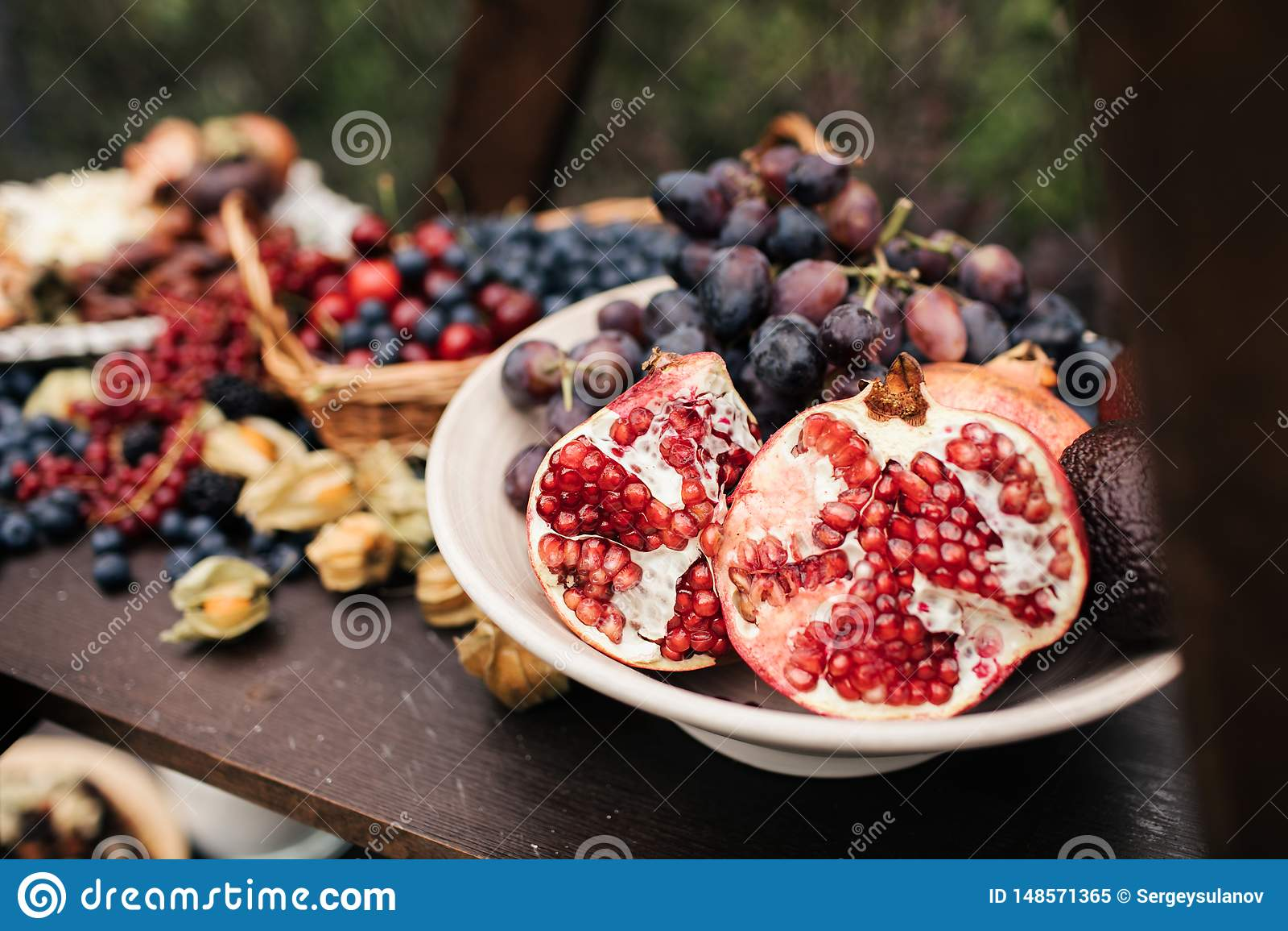 Granat?pple och druvor i en platta p? tr?tabellen