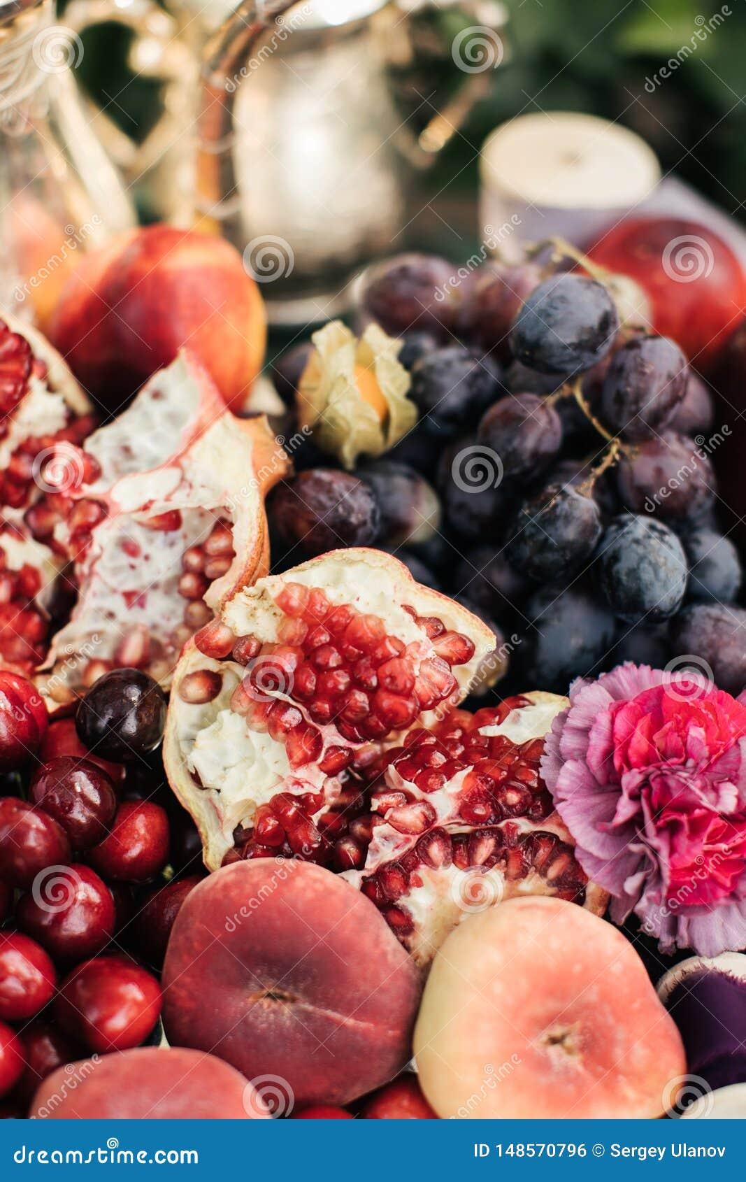 Granatapfel und Trauben in einer Platte auf dem Holztisch