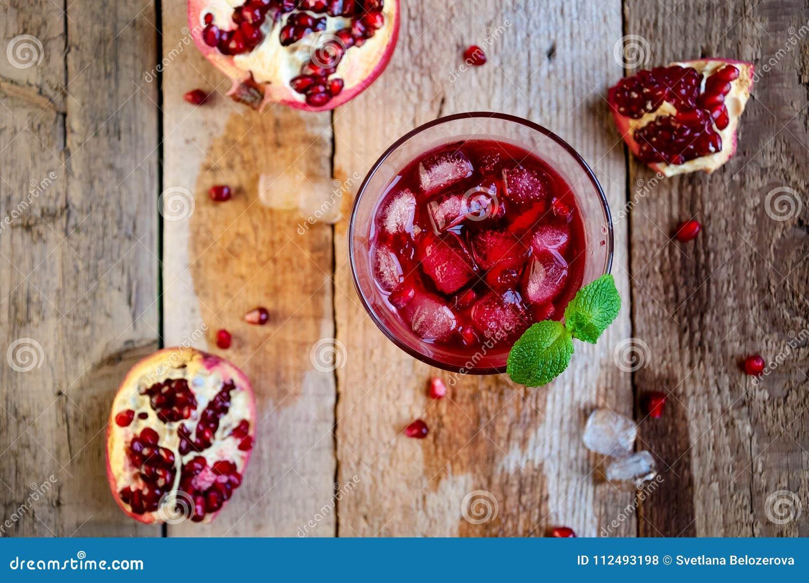Granatowa koktajl z lód owoc na Drewnianym stole i mennicą Ponowny