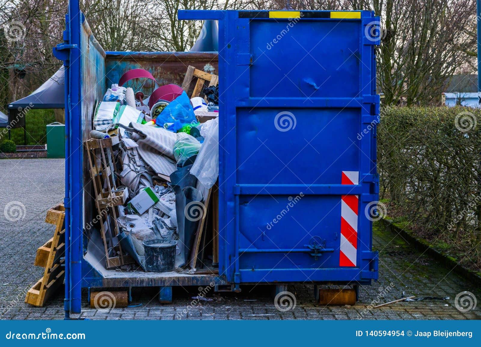 Grand bac à vidange encombrant, plein des déchets, réutilisant le concept, conscience d environnement