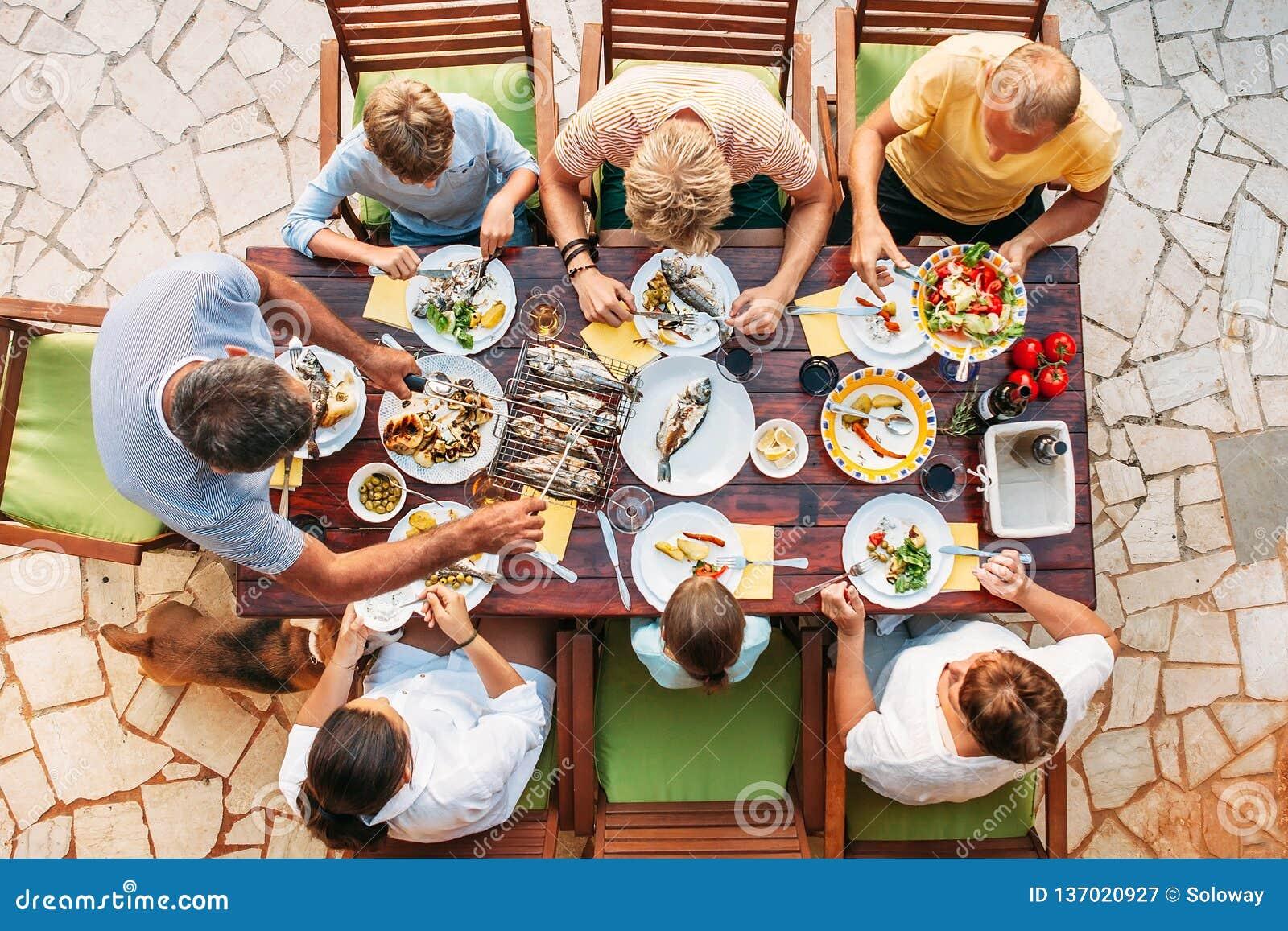 Grand dîner de famille de miltigeneration dans le processus Image verticale de vue supérieure sur la table avec la nourriture et