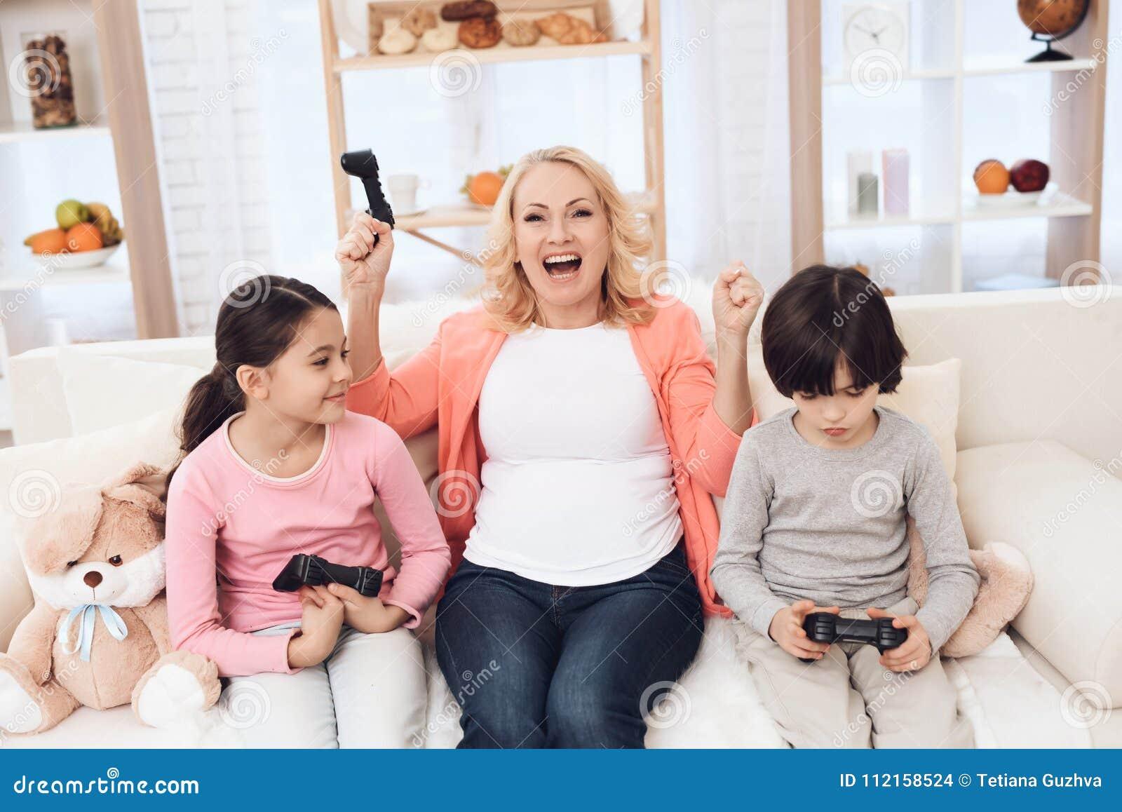 Grand-mère joyeuse avec les petits-enfants gais jouant sur la console de jeu se reposant sur le divan