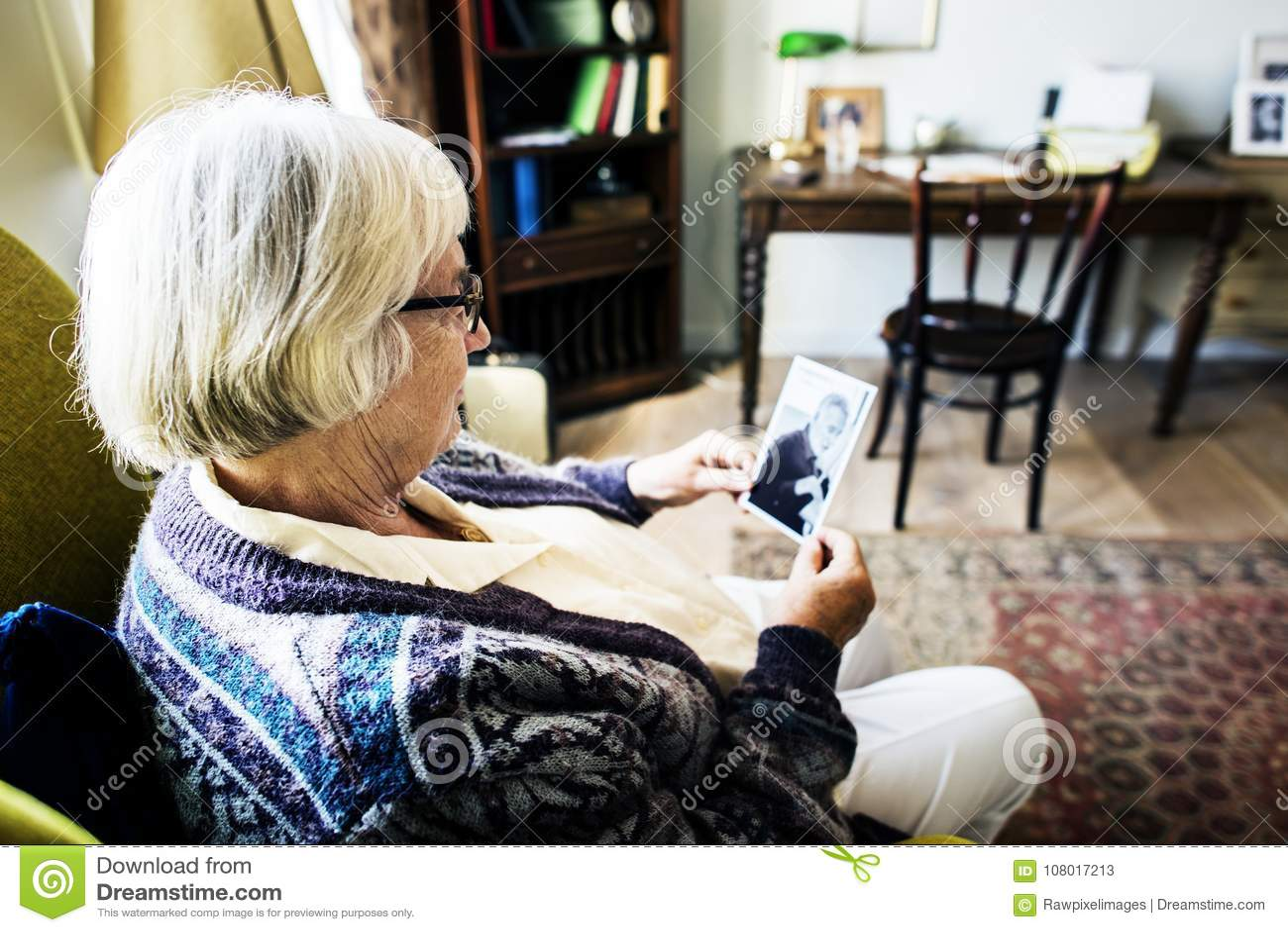 Grand-mère reposant et regardant sa photo du ` s de mari
