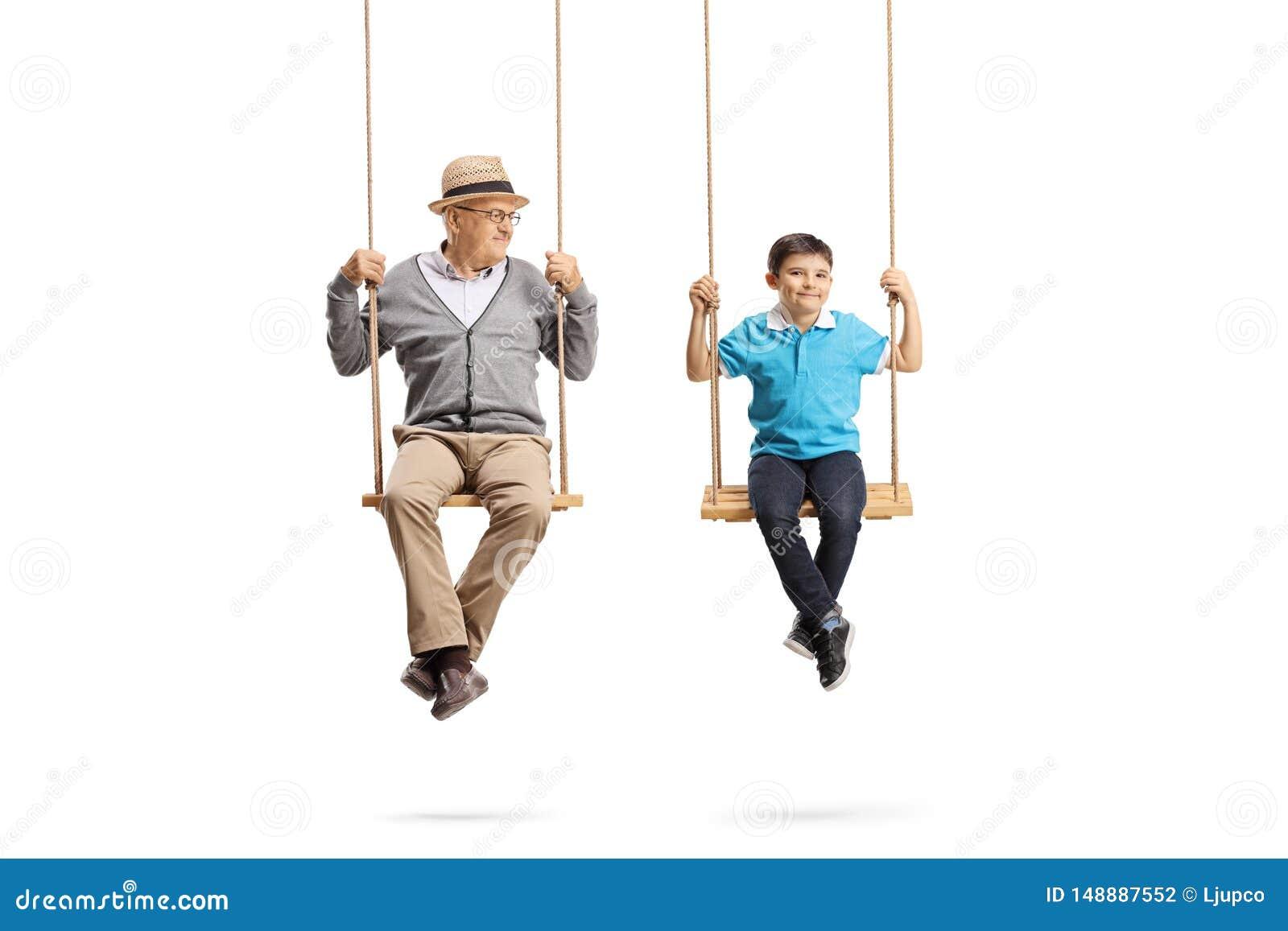 Grand-p?re regardant son petit-fils et s asseyant sur les oscillations en bois