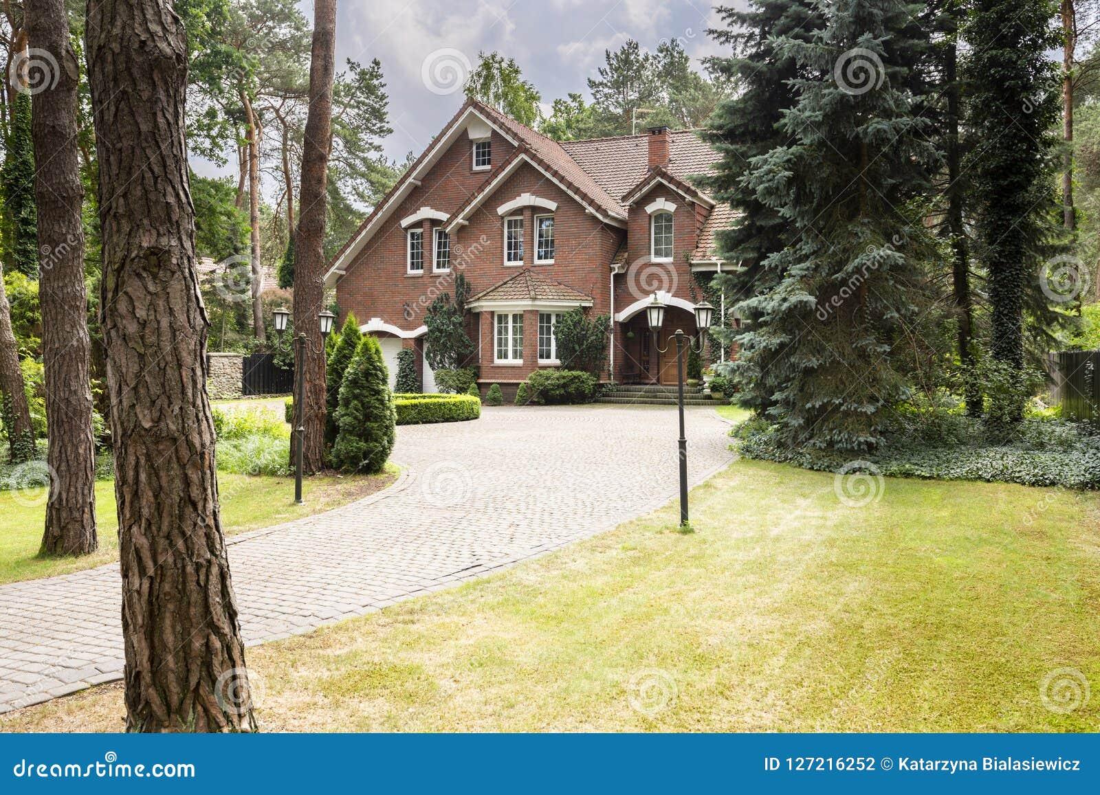 Grand, rural domaine avec la façade de brique et pelouse verte se tenant dedans