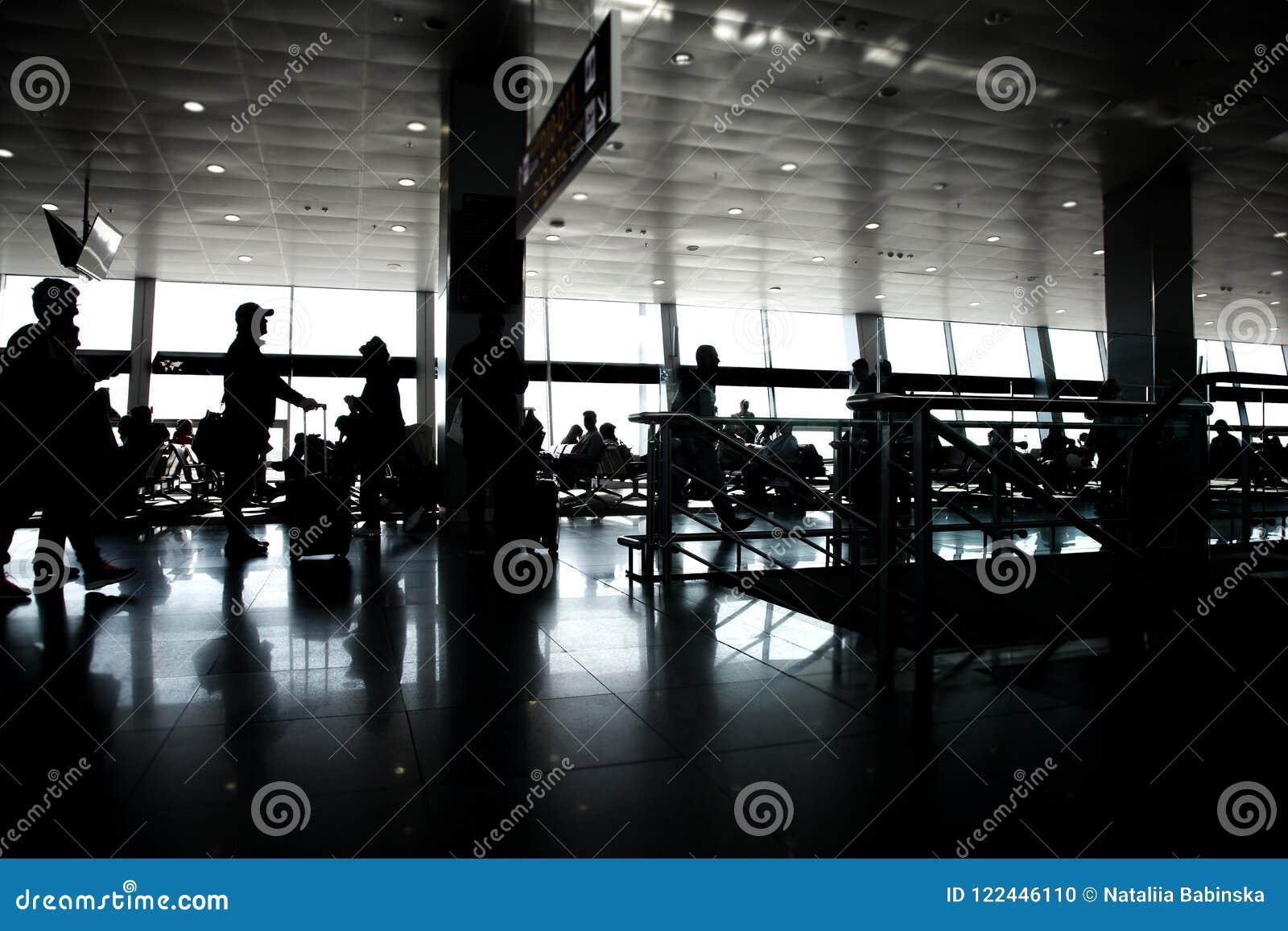 Grand siège fenêtre reposant les passagers blancs noirs du soleil de silhouette attendant l aéroport de terminal de porte