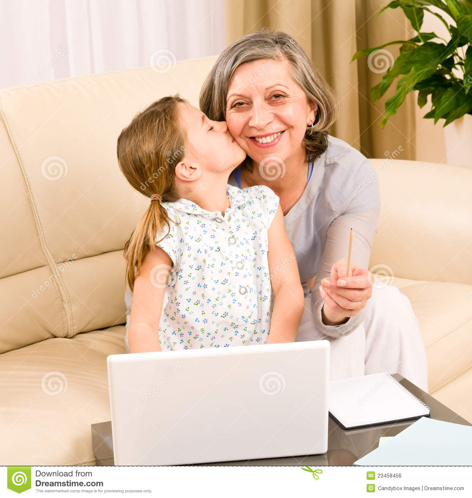 Granddaughter giving kiss to grandmother smiling together on sofa.