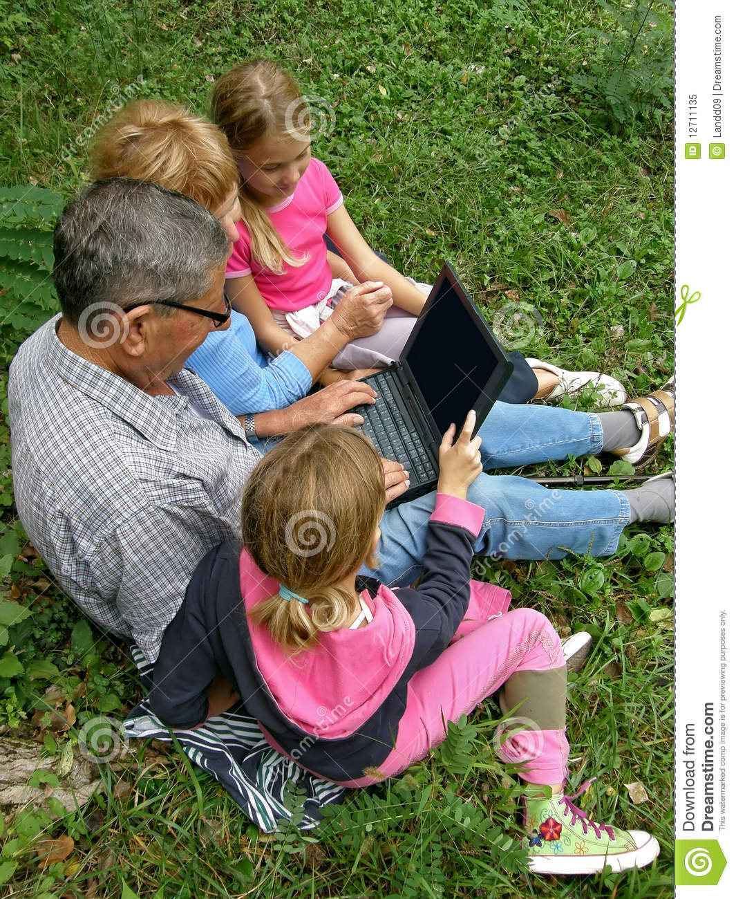 Granddaughter and grandparent with laptop