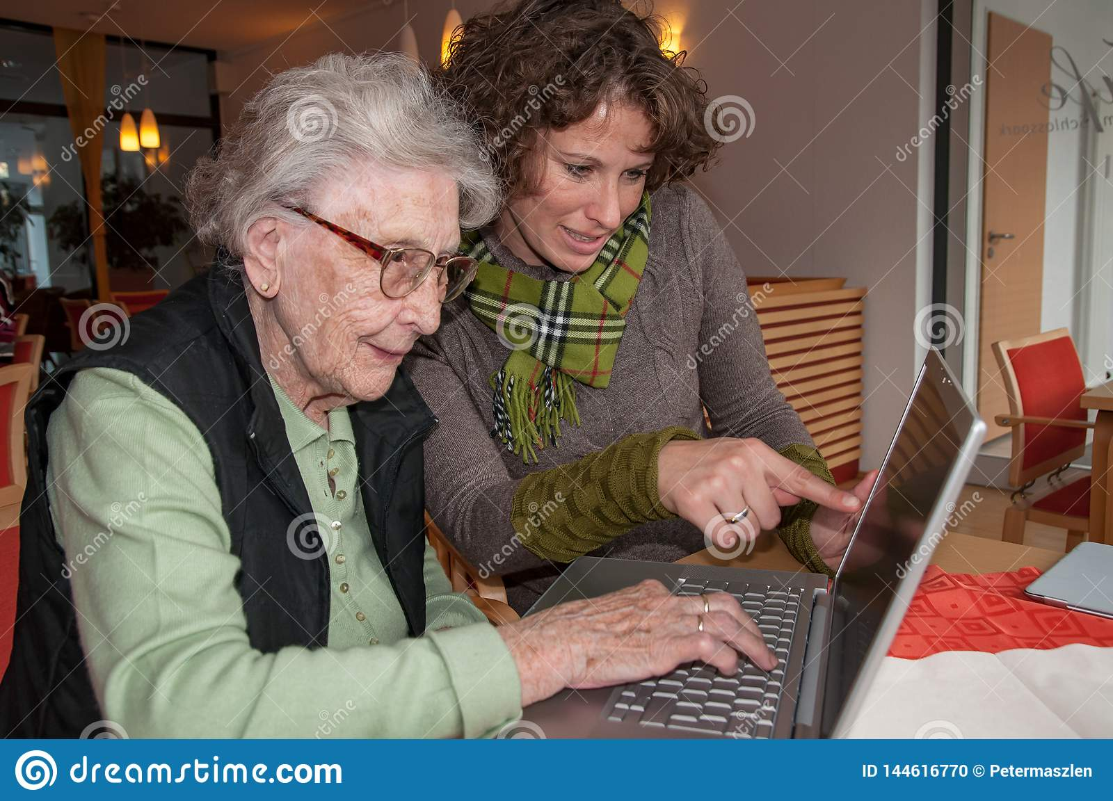 Young woman helping senior woman working with laptop