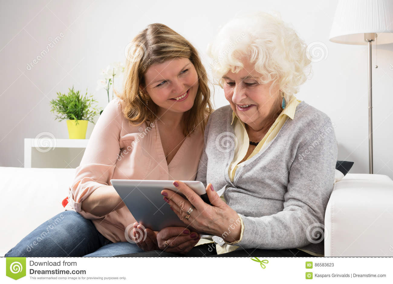 Granddaughter teaching grandmother how to use tablet