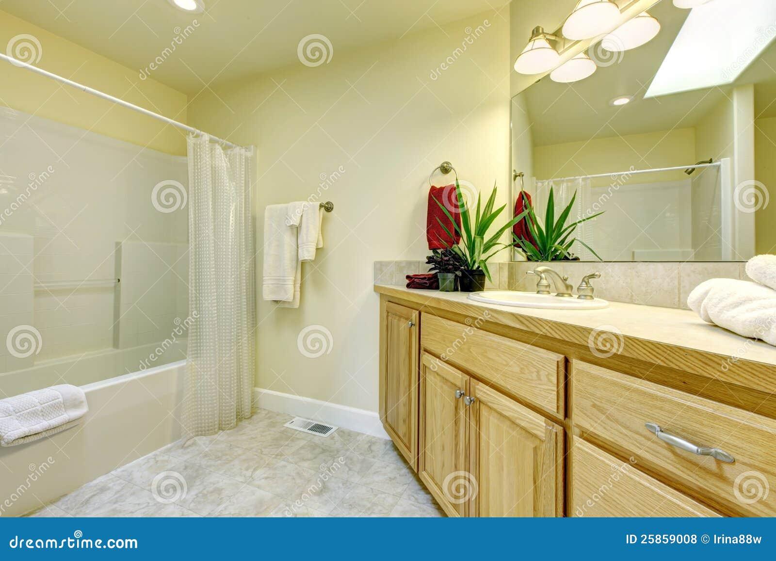 Grande banheiro simples com o assoalho do bege do wih dos gabinetes da  #763114 1300 957