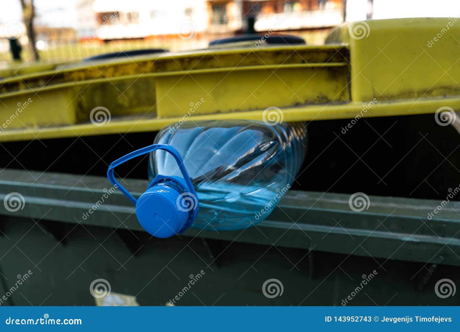 Grande bouteille en plastique bleue dans une poubelle verte jaune - r?utilisez pour la nature