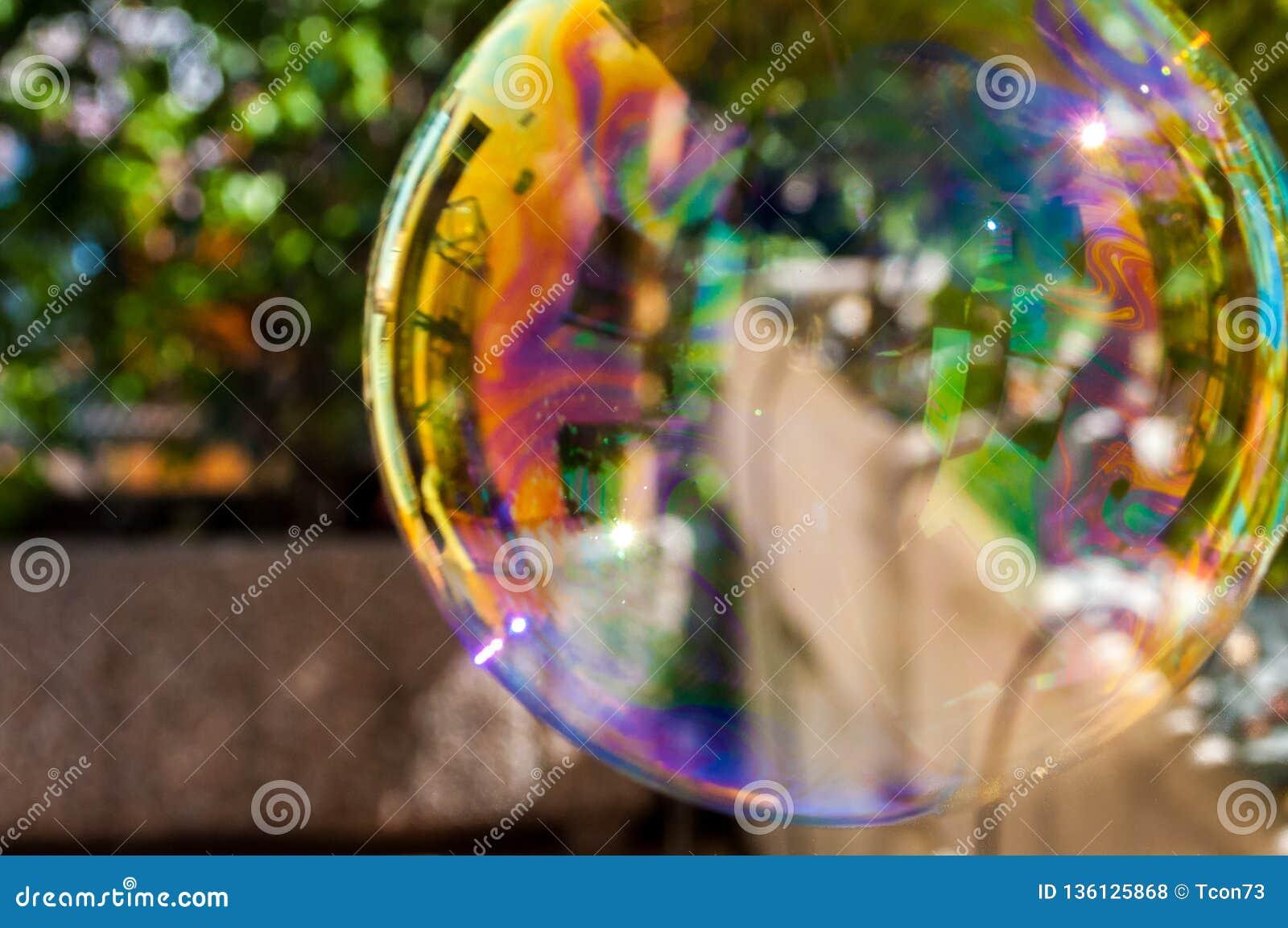Grande bulle de jeu de savon dans le jardin avec des couleurs d arc-en-ciel