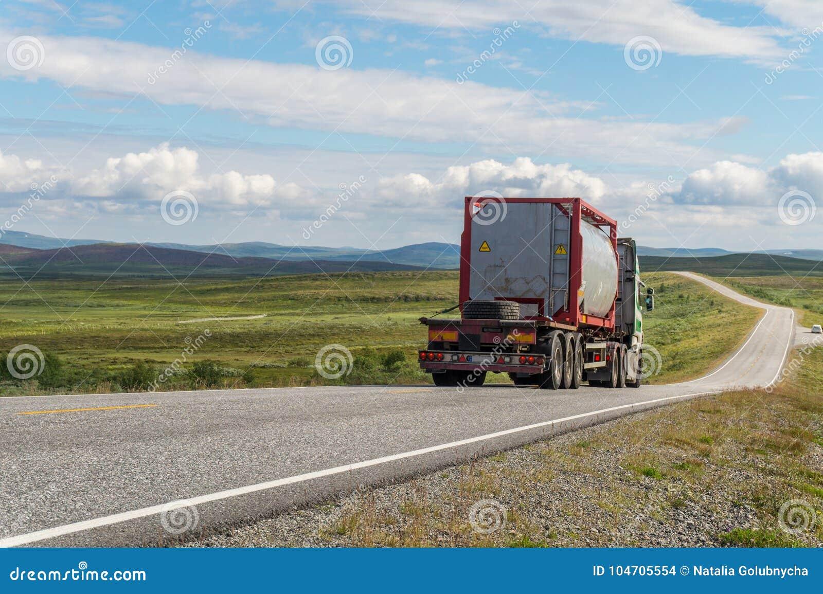 Grande camion cisterna sulla strada su un fondo di un prato verde e delle nuvole
