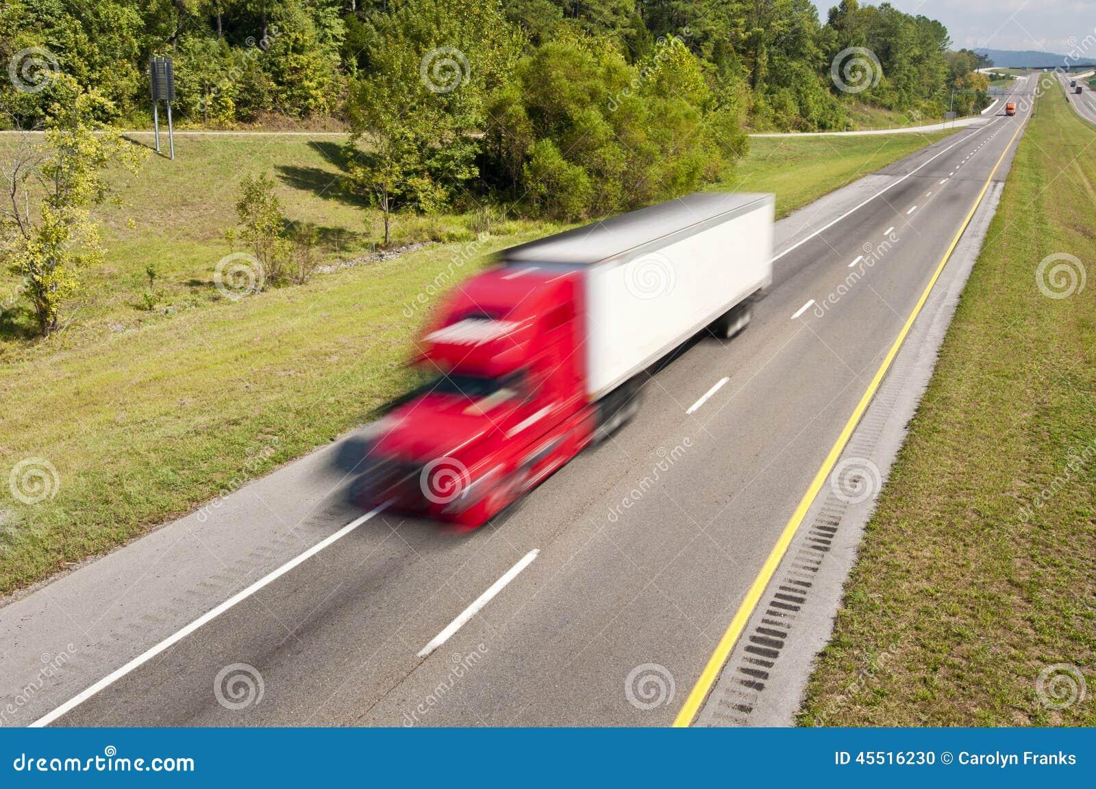 Grande camion rosso che accelera giù la strada principale