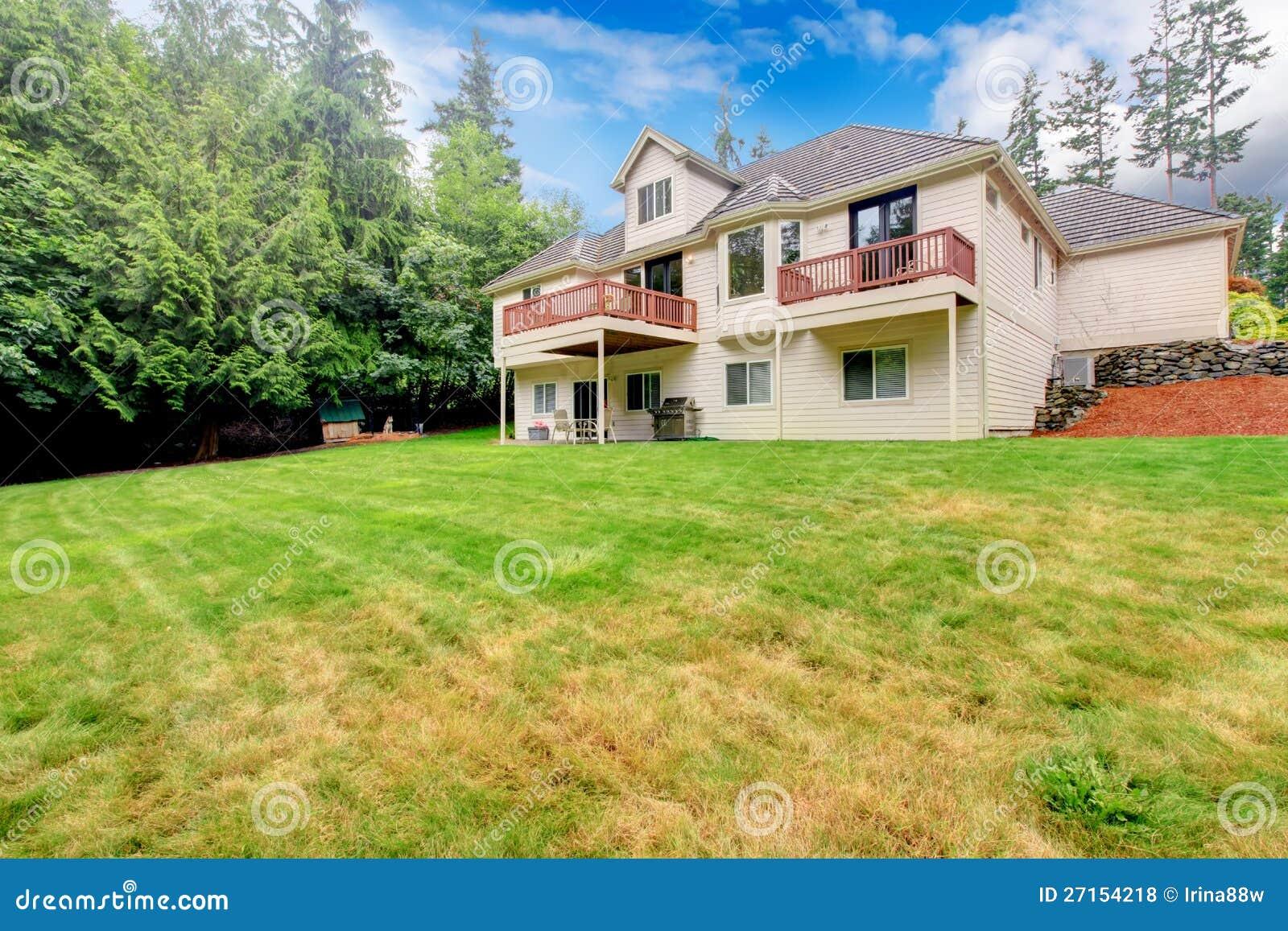 Grande casa beige dal cortile con erba grande zona del for Piani casa del cortile