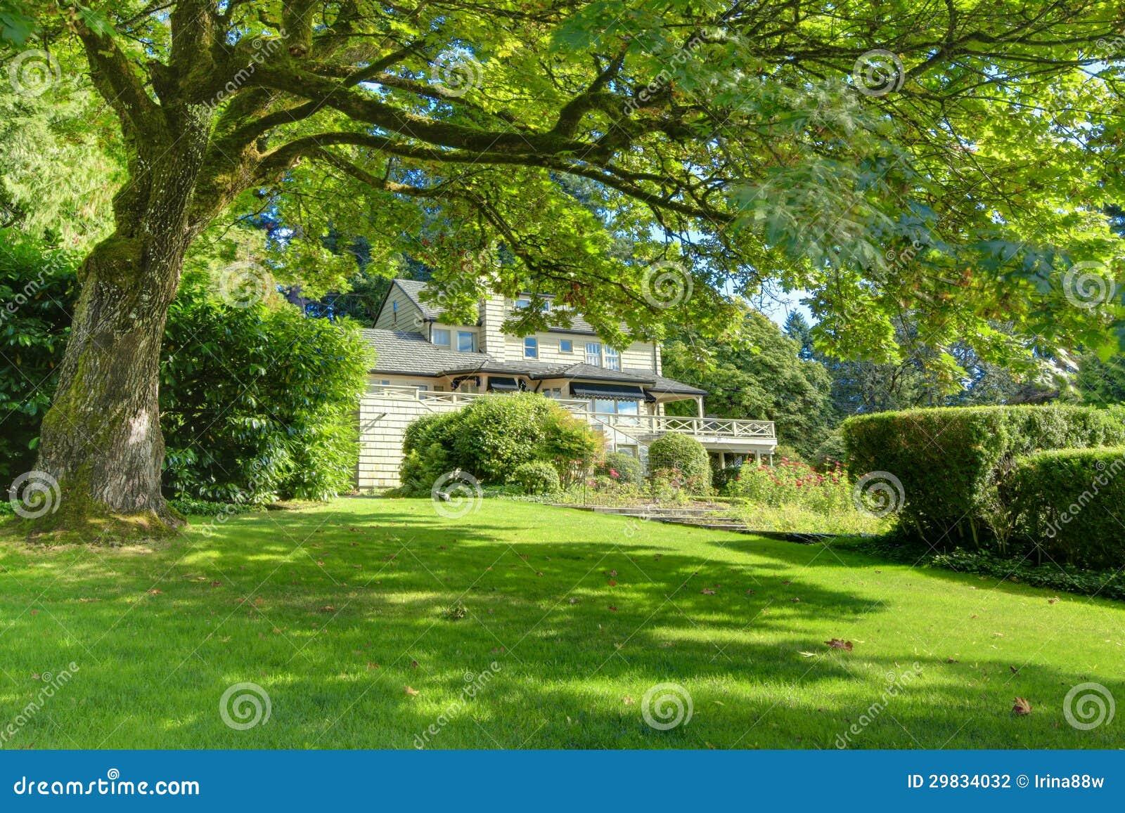 Grande casa marrom exterior com o jardim verde do verão.